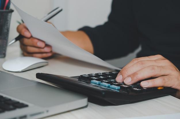 Hombre de negocios con calculadora en un escritorio. conceptos de inversión, impuestos y finanzas empresariales.