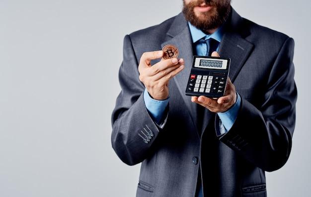 Hombre de negocios con calculadora en manos y tipo de cambio de riqueza de bitcoin de criptomoneda. foto de alta calidad