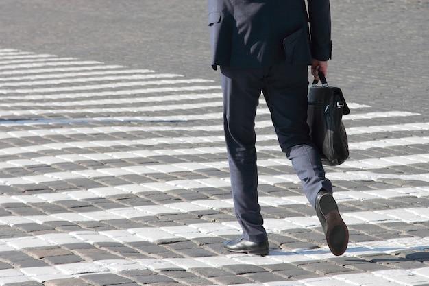 Hombre de negocios camina sobre un paso de peatones