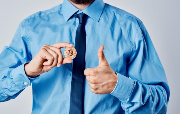 Hombre de negocios en una camisa azul con una moneda en su mano modelo de finanzas bitcoin criptomoneda