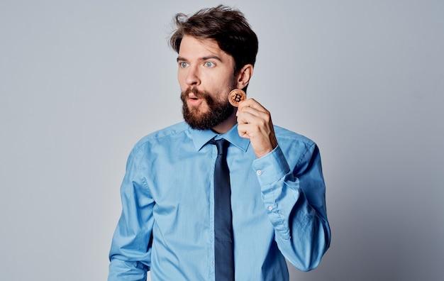 Hombre de negocios con una camisa azul con una moneda en sus manos bitcoin fondo gris