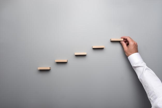 Hombre de negocios en camisa blanca construyendo un gráfico o una escalera de éxito en la pared gris.