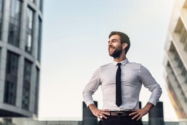 El hombre de negocios en una camisa blanca y una corbata sonríe contra el fondo de la ciudad en un su
