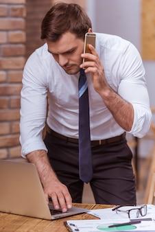 El hombre de negocios en la camisa blanca está hablando en el teléfono móvil.