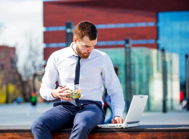 Hombre de negocios en camisa y corbata con caja de almuerzo de ensalada