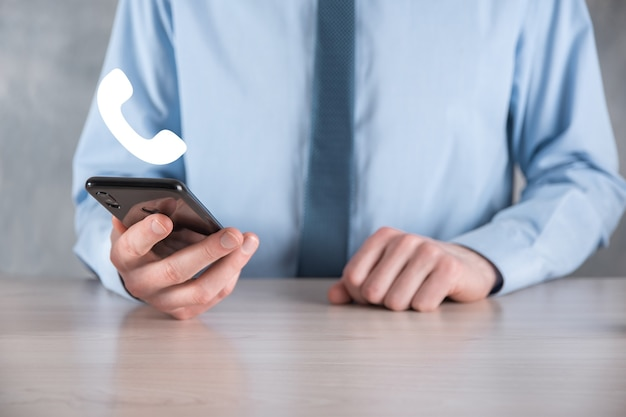 Hombre de negocios en una camisa con corbata en la pared gris mantenga el icono de teléfono. llame ahora centro de soporte de comunicación empresarial concepto de tecnología de servicio al cliente.