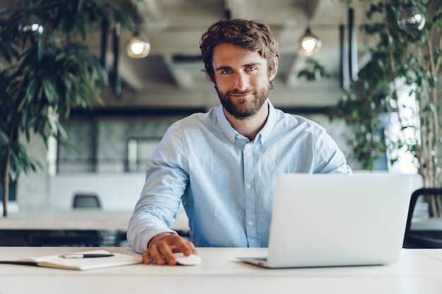 Hombre de negocios en camisa trabajando en su computadora portátil en una oficina. oficina de espacio abierto