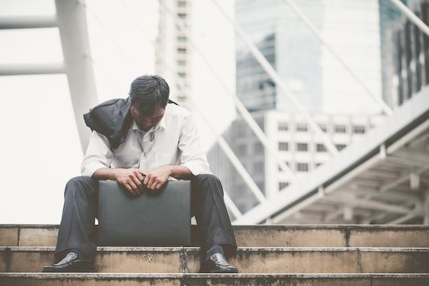 Hombre de negocios cansado o tensionado que se sienta en la calzada en la ciudad después de su trabajo.