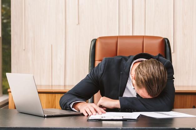 Hombre de negocios cansado que duerme con el ordenador portátil en la tabla en la oficina