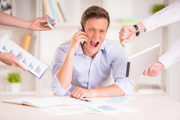 Hombre de negocios cansado en su oficina está gritando.