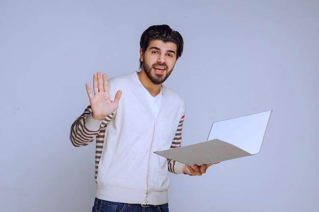 Hombre de negocios con una carpeta de proyecto dando la mano y saludando a sus colegas.