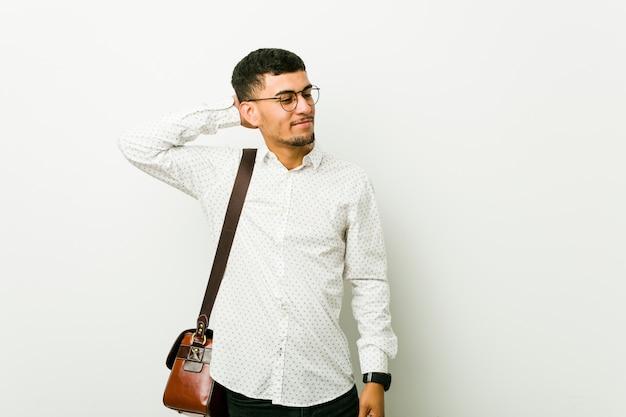 Hombre de negocios casual hispano joven tocando la parte posterior de la cabeza, pensando y haciendo una elección.