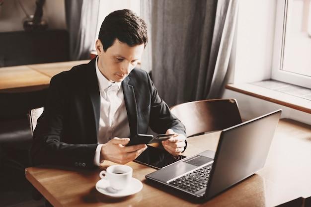 Hombre de negocios caucásico adulto lindo que usa una tarjeta de crédito y un teléfono inteligente mientras toma el almuerzo en su hora del almuerzo.