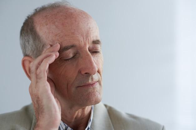 Hombre de negocios caucásico anciano masajeando el templo con los ojos cerrados