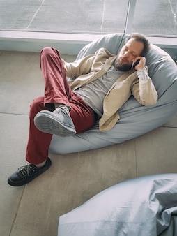Hombre de negocios caucásico con barba esperando su vuelo en el aeropuerto y hablando por teléfono acostado