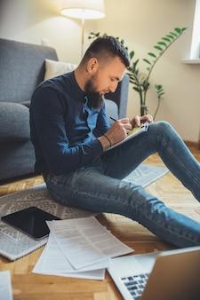 Hombre de negocios caucásico con barba larga está sentado en el suelo y trabajando con algunos documentos usando una computadora portátil