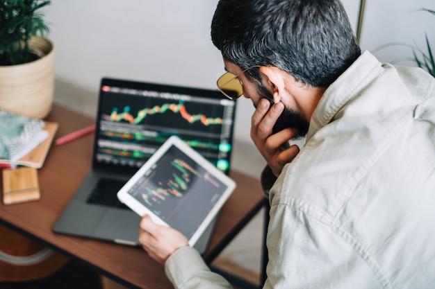 Hombre de negocios caucásico comerciando en línea, utilizando tecnología informática, mirando el comercio bursátil y analizando