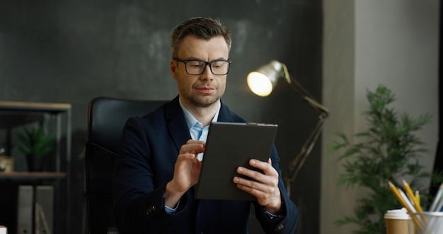 Hombre de negocios caucásico en gafas sosteniendo y usando el dispositivo de tableta en las manos. mensajes de texto masculinos y escribiendo en la pantalla y pensando en el gabinete.