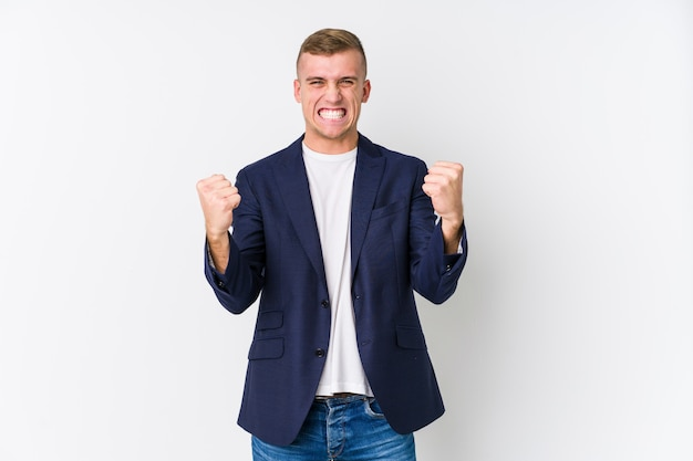 Hombre de negocios caucásico joven animando despreocupado y emocionado. concepto de victoria