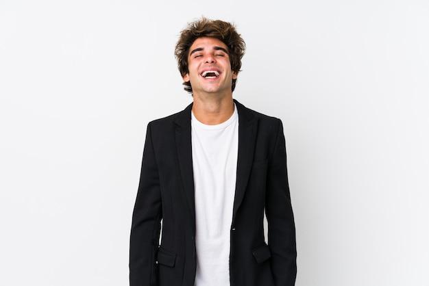 El hombre de negocios caucásico joven contra una pared blanca aisló la risa relajada y feliz, el cuello estirado mostrando los dientes.