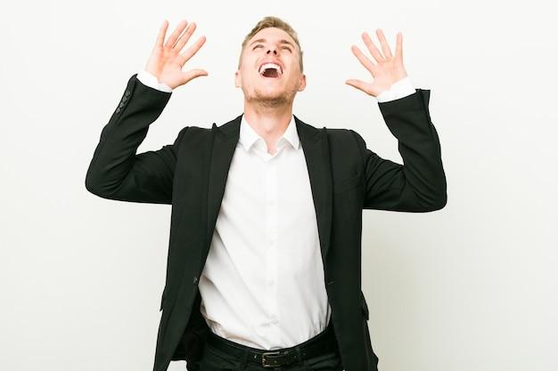 Hombre de negocios caucásico joven gritando hacia el cielo, mirando hacia arriba, frustrado.