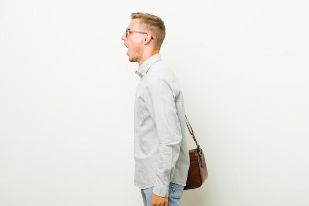 Hombre de negocios caucásico joven gritando hacia un espacio en blanco