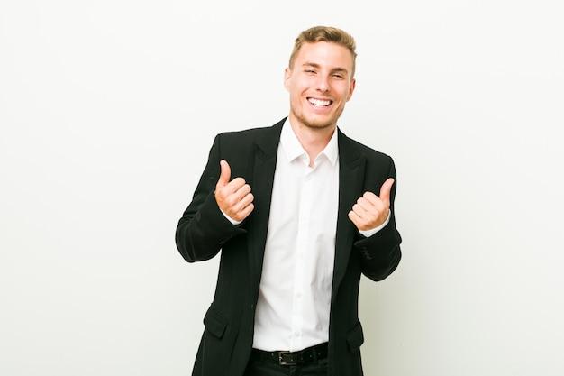 Hombre de negocios caucásico joven levantando ambos pulgares, sonriente y confiado.