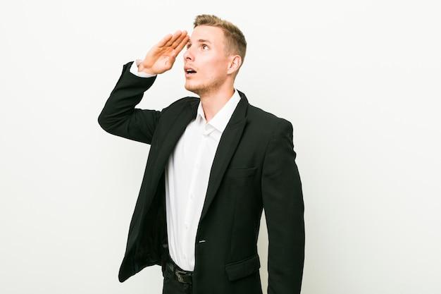 Hombre de negocios caucásico joven mirando lejos manteniendo la mano en la frente.