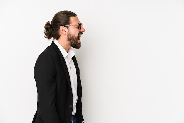 Hombre de negocios caucásico joven en una pared blanca gritando hacia un espacio en blanco