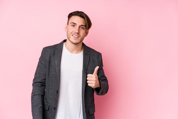 Hombre de negocios caucásico joven posando aislado sonriendo y levantando el pulgar hacia arriba