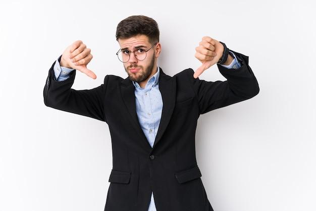 Hombre de negocios caucásico joven posando en una pared blanca aislada hombre de negocios caucásico joven mostrando el pulgar hacia abajo y expresando disgusto.