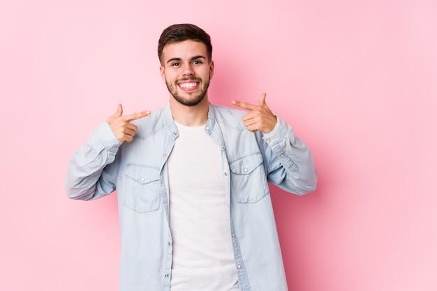 El hombre de negocios caucásico joven que presenta en una pared blanca aisló sonrisas, señalando los dedos en la boca.