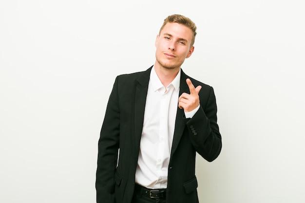El hombre de negocios caucásico joven que señala con el dedo a usted como invitando se acerca.