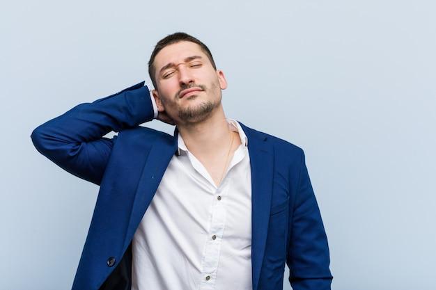 Hombre de negocios caucásico joven que sufre dolor de cuello debido al estilo de vida sedentario.