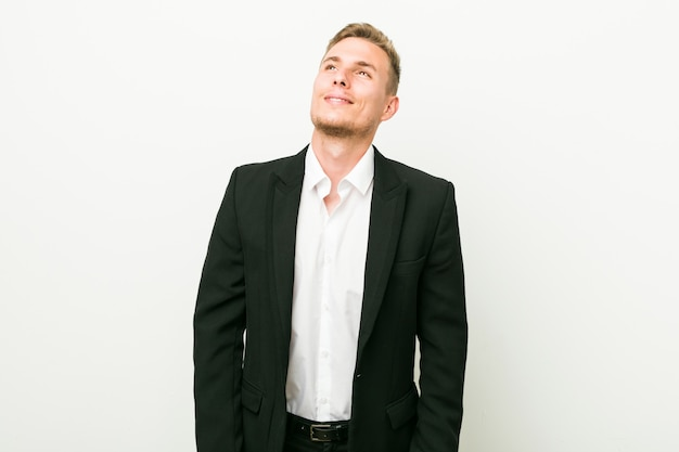 Hombre de negocios caucásico joven soñando con lograr objetivos y propósitos