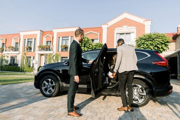 Hombre de negocios caucásico joven en traje abriendo la puerta del coche negro para sus colegas, hombre africano y mujer caucásica. al aire libre, edificios de centros de negocios
