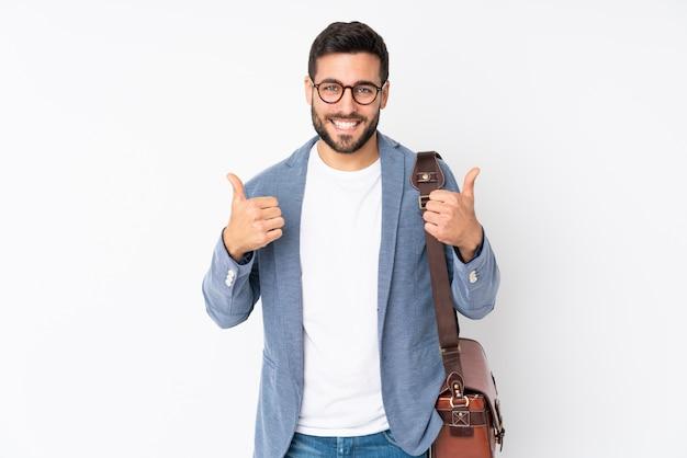 Hombre de negocios caucásico en pared blanca dando un gesto de pulgares arriba