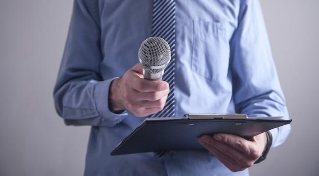 Hombre de negocios caucásico de pie en la oficina con micrófono.
