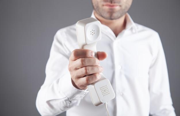 Hombre de negocios caucásico que sostiene el receptor del teléfono.