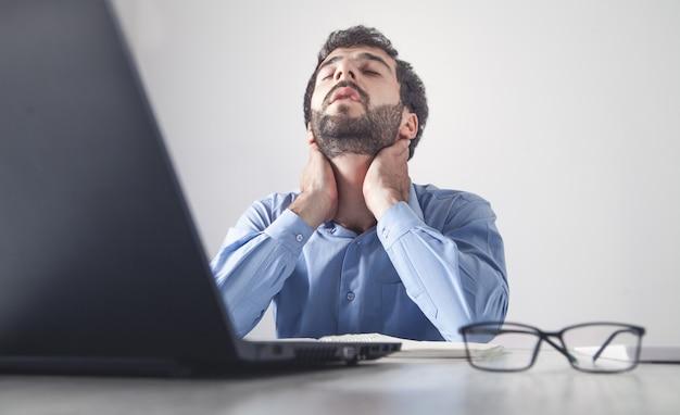Hombre de negocios caucásico que sufre de dolor de cuello en la oficina