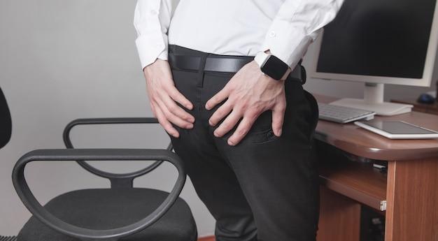 Hombre de negocios caucásico que sufre de hemorroides en la oficina.