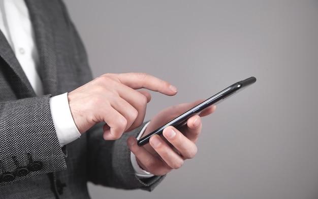Hombre de negocios caucásico con smartphone en la oficina.