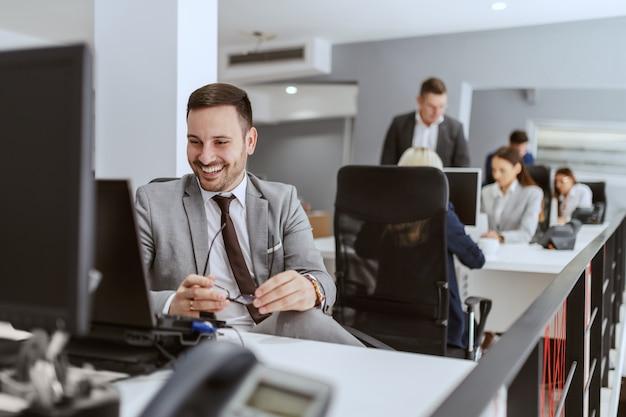 Hombre de negocios caucásico sonriente motivado satisfecho sentado en su lugar de trabajo y mirando la computadora con anteojos en las manos.