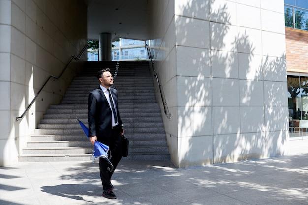 Hombre de negocios caucásico en traje con paraguas caminando delante de la oficina y la escalera
