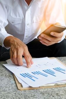 Hombre de negocios la celebración de teléfono móvil con el análisis gráfico financiero en tableta, concepto de estrategia, idea de negocio, concepto de negocio