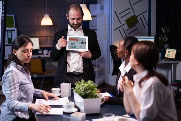 Hombre de negocios centrado que muestra la presentación de gráficos corporativos usando tableta trabajando en ideas de empresa