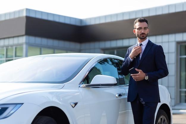Hombre de negocios cerca del coche. elegante joven empresario de pie cerca del coche blanco en la mañana