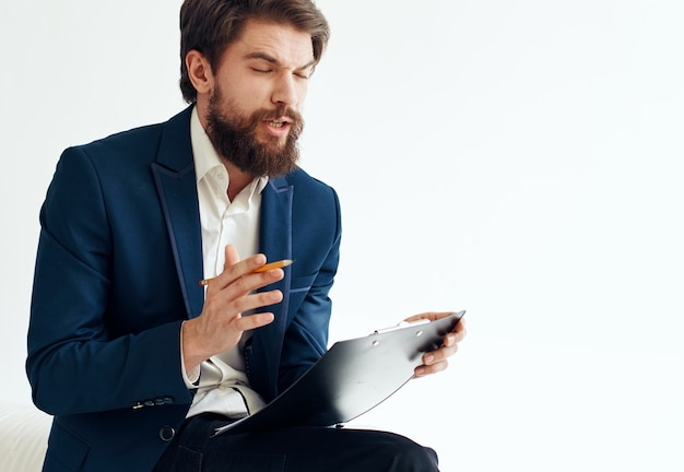 Hombre de negocios con una chaqueta azul y una camisa blanca con documentos en una carpeta sobre un fondo claro