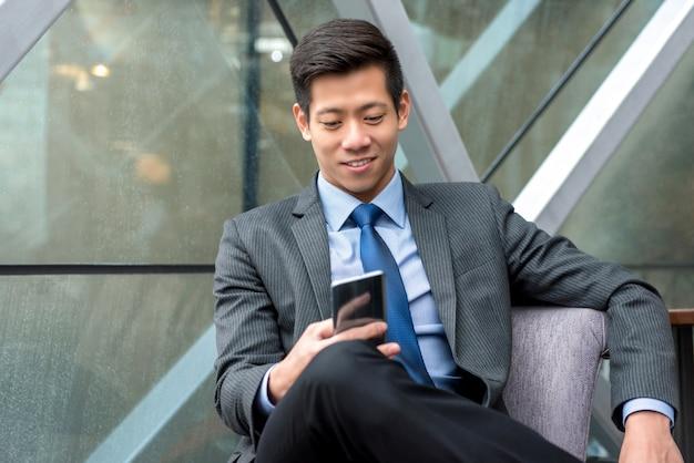 Hombre de negocios chino asiático hermoso joven que usa smartphone mientras que se sienta en el salón de la oficina