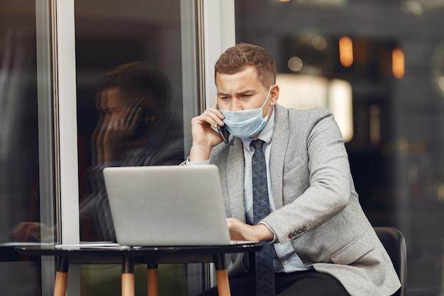 Hombre de negocios en una ciudad. persona con máscara. chico con laptop.